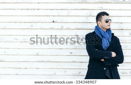 Handsome man in coat on white wooden background with blank space,selective focus - stock photo