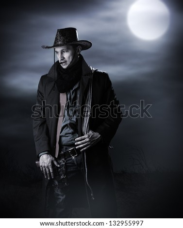 Handsome man in cowboy costume stay in steppe at night with full moon. Vampire Hunter - stock photo