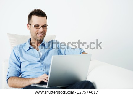 Handsome man in glasses using laptop on sofa - stock photo