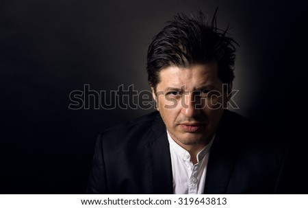Handsome man in his 40's looking in the camera with a serious attitude. Wearing white shirt and a black jacket. Slight color grading - stock photo