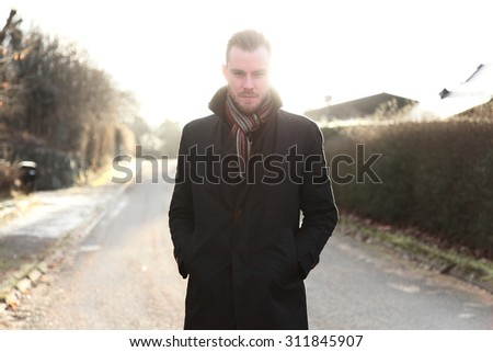 Handsome man in his 20s, standing outside on a cold winter day wearing a black jacket and scarf looking straight into camera. Pensive with the sun straight behind him. - stock photo