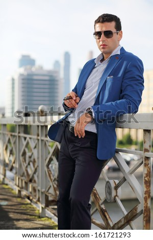 Handsome man in jacket and sunglasses with cigar stands near railings. - stock photo