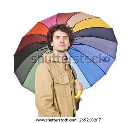 Handsome man in light brown vintage raincoat holding colorful umbrella. - stock photo