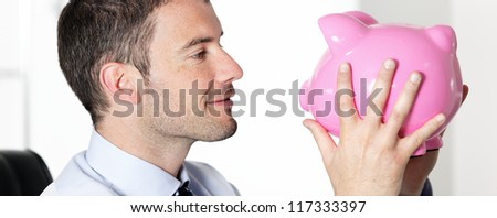 handsome man in office kissing a pink piggy bank - stock photo