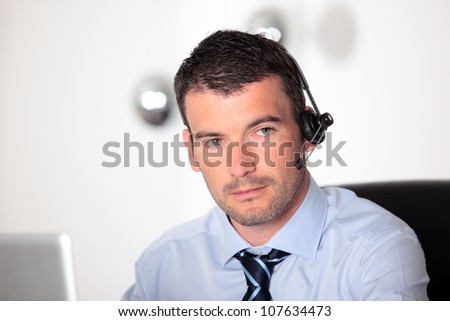 handsome man in office with headset and computer - stock photo