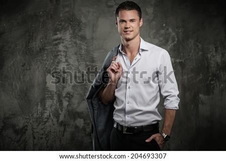 Handsome man in shirt against grunge wall holding jacket over shoulder  - stock photo