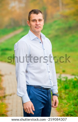 handsome man in shirt and trousers smiling - stock photo