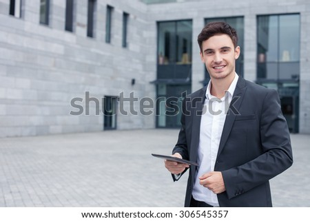 Handsome man in suit is standing near his office and smiling. He is holding a tablet and looking at the camera with joy. Copy space in left side - stock photo