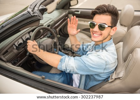 Handsome man in sunglasses driving by cabriolet, looking at camera with hand up and smiling. - stock photo
