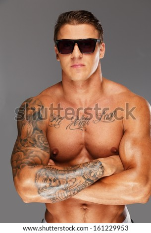 Handsome man in sunglasses with muscular tattooed torso - stock photo