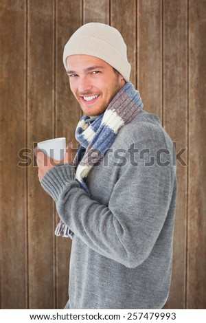 Handsome man in winter fashion holding mug against wooden planks background - stock photo