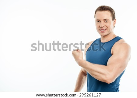 Handsome man is flexing his bicep. He is smiling and looking at the camera. Isolated on background and there is copy space in left side - stock photo