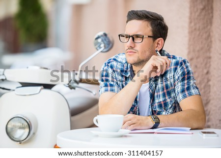 Handsome man is relaxing in cafe and drinking coffee. His vintage scooter is standing on background. - stock photo