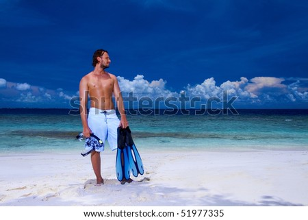Handsome man is standing on the beach holding fin - stock photo