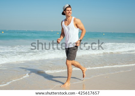 Handsome man jogging on the beach. - stock photo
