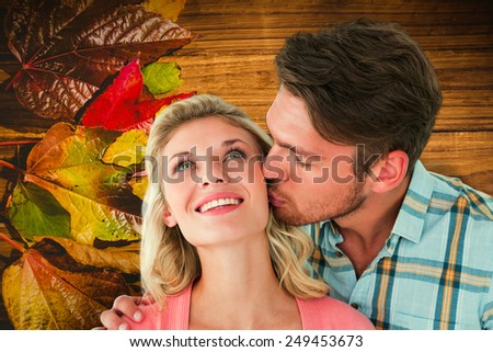 Handsome man kissing girlfriend on cheek against wooden table with autumn leaves - stock photo