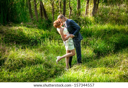 handsome man kissing sexy woman in field - stock photo