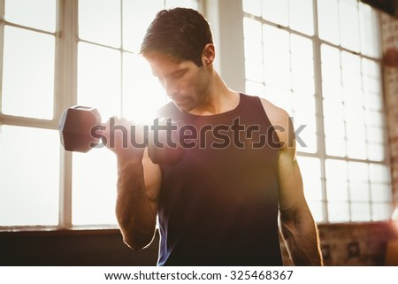 Handsome man lifting dumbbell at gym - stock photo