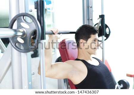Handsome man lifting heavy weights at the gym - stock photo