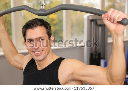 Handsome man lifting weights in a gym - stock photo