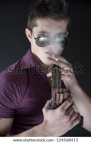 handsome man lights a cigarette - stock photo