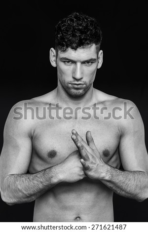 Handsome man looking ahead with his fists up against each other, on a black background, in black and white  - stock photo