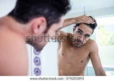 Handsome man looking at his hair in bathroom - stock photo