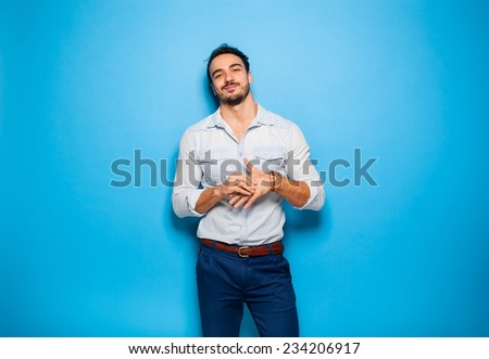 handsome man looking confident and relaxed on blue background - stock photo
