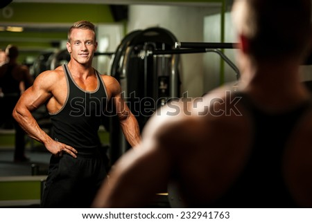 Handsome man looking in mirror after body building workout - stock photo