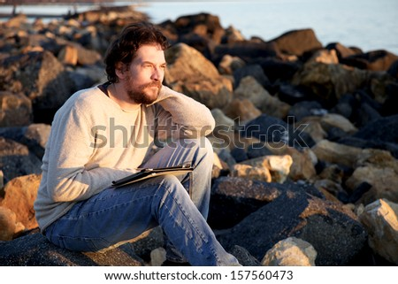 Handsome man looking sunset - stock photo