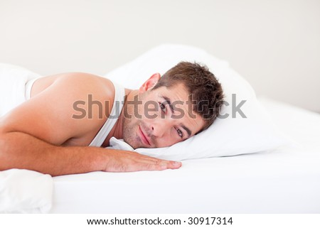 Handsome man lying in his bed - stock photo