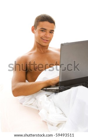 handsome man lying in the bed with lap top - stock photo