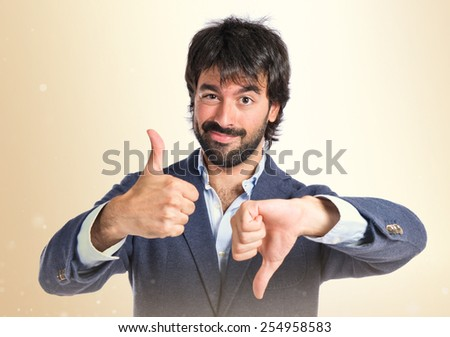Handsome man making a good-bad sign over white background - stock photo