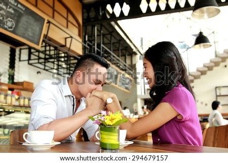 handsome man man kissing his girlfriend hands while dating - stock photo