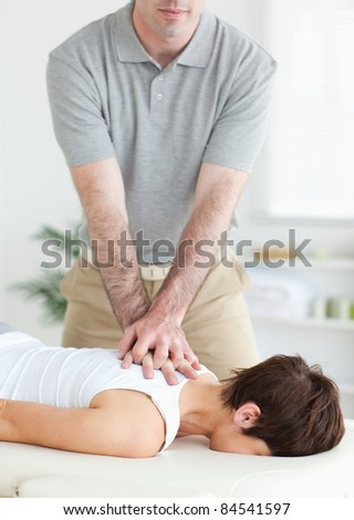 Handsome Man massaging a cute woman's neck in a room - stock photo