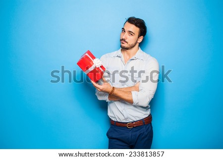 handsome man on blue background with red christmas gift on blue background - stock photo