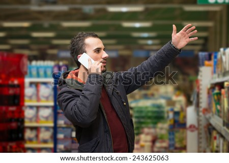 Handsome Man On Mobile Phone At Supermarket - stock photo