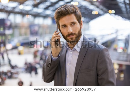 Handsome man on the mobile phone in hall station - stock photo