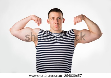 Handsome man on white. Muscular man in a striped vest, in casual clothes posing on light background. strength, fitness, fashion, health, muscles. Young strong man. - stock photo
