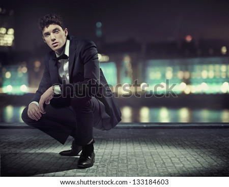 Handsome man over night city background - stock photo