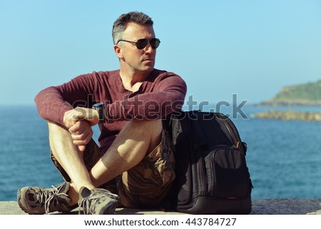 Handsome man over sea view. Outdoor male portrait. Trip, vacation, holiday, tourism, leisure, lifestyle, summer time concept. - stock photo