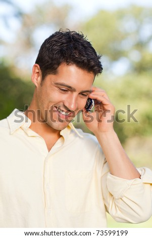 Handsome man phoning in the park - stock photo