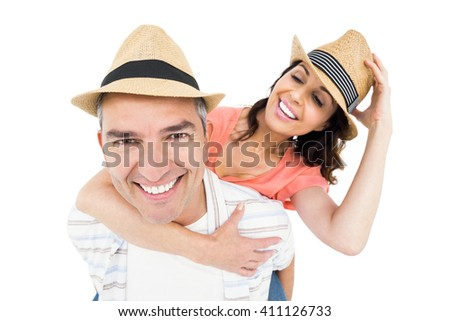 Handsome man piggy backing his wife against white background - stock photo