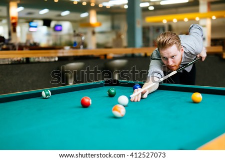 Handsome man playing billiards and aiming at ball - stock photo
