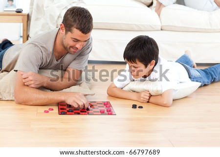 Handsome man playing checkers with his son lying on the floor at home - stock photo