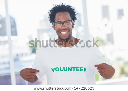 Handsome man pointing to his volunteer tshirt in a modern office - stock photo