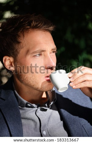 Handsome man portrait drinking espresso at cafe enjoying coffee. Close up portrait of male business man sitting outdoors drinking from espresso cup in suit jacket. Handsome modern city guy. - stock photo