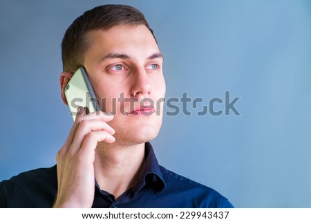 Handsome man portrait talking at the cell phone on blue background - stock photo