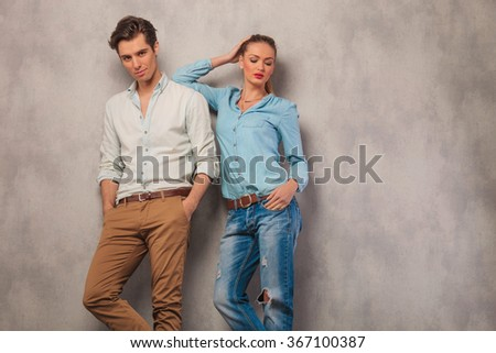 handsome man pose in studio background with hands in pockets while woman is resting her arm on his shoulder while posing with hand in pocket - stock photo
