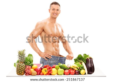Handsome man posing behind a table with vegetables isolated on white background - stock photo
